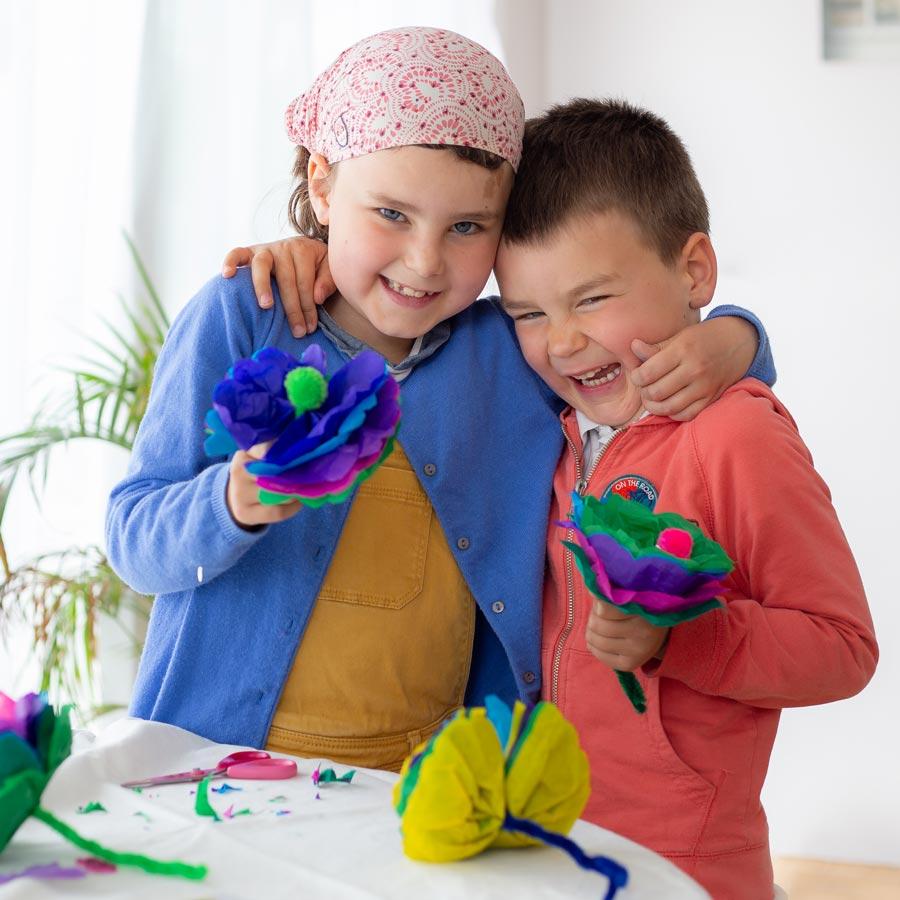 Deux enfants qui rigolent et sont heureux après avoir fabriqué une fleur en papier de soie - Activité, DIY & matériel créatif pour enfants proposé dans la box pour enfants PICADELO