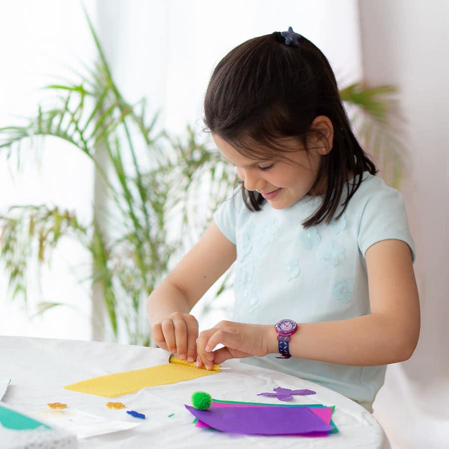 Une petite fille concentrée en train de fabriquer une bougie en cire d'abeille - Activité ludique & matériel inclus dans la box pour enfant Picadelo
