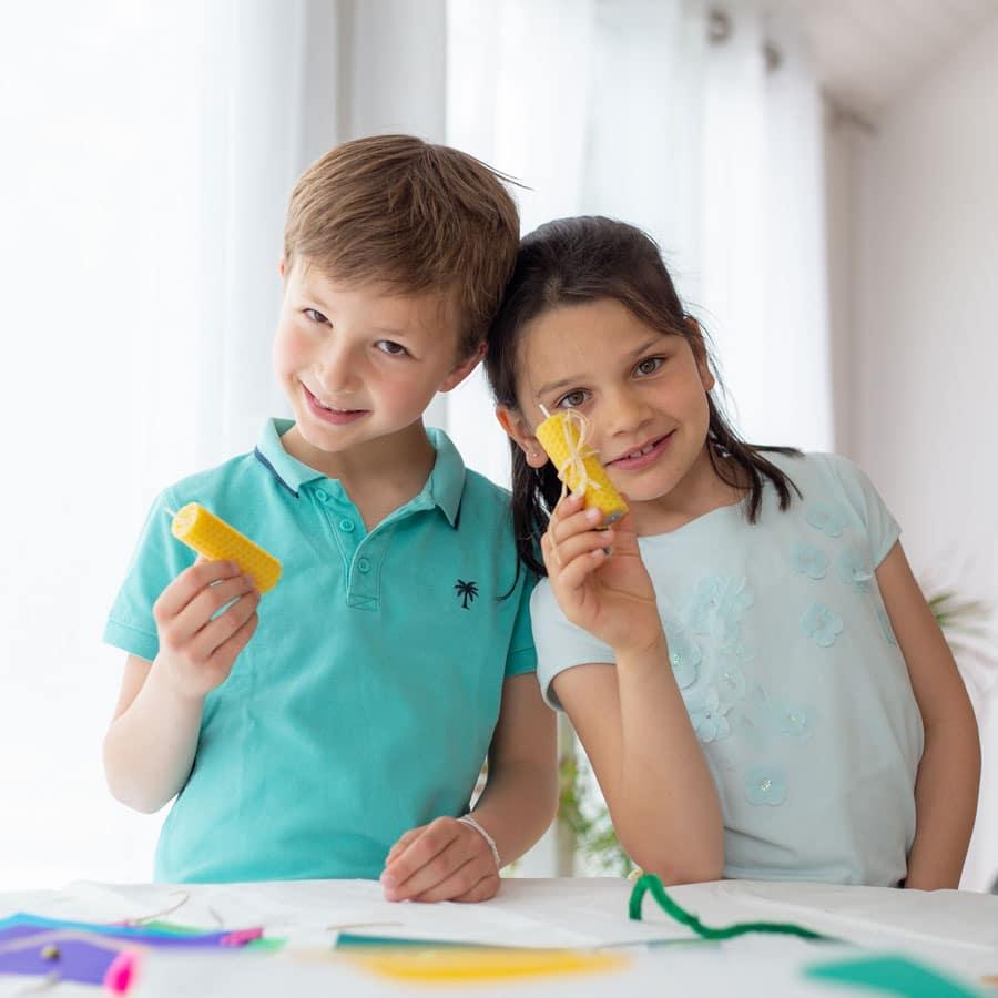 Deux enfants beaux et souriants qui montrent avec fierté leur création : une bougie en cire - Activité et matériel proposé dans la box Picadelo