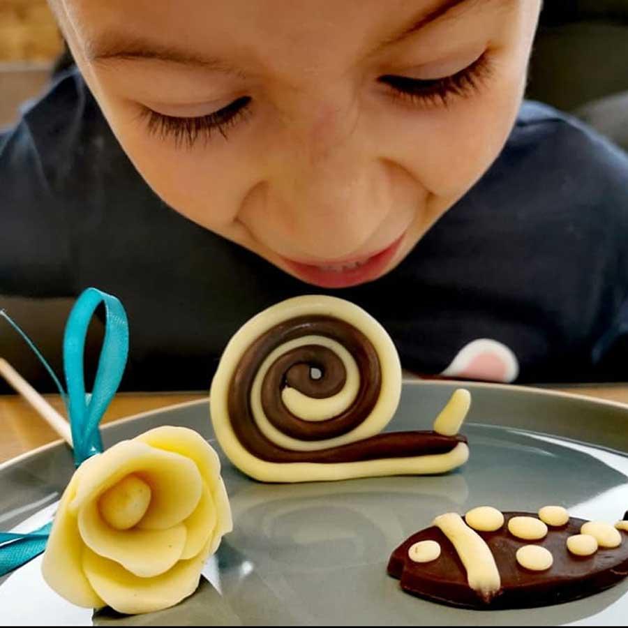 Petit garçcon - enfant - montre ses réalisation en pâte à modeler au chocolat : une fleur, un escargot et un poisson modeler tout seul. Enfant heureux