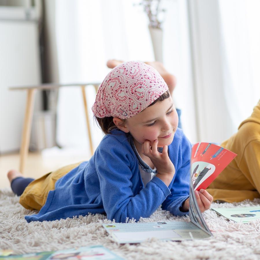 Une petite fille lit, regarde, un magazine, un livre jeunesse