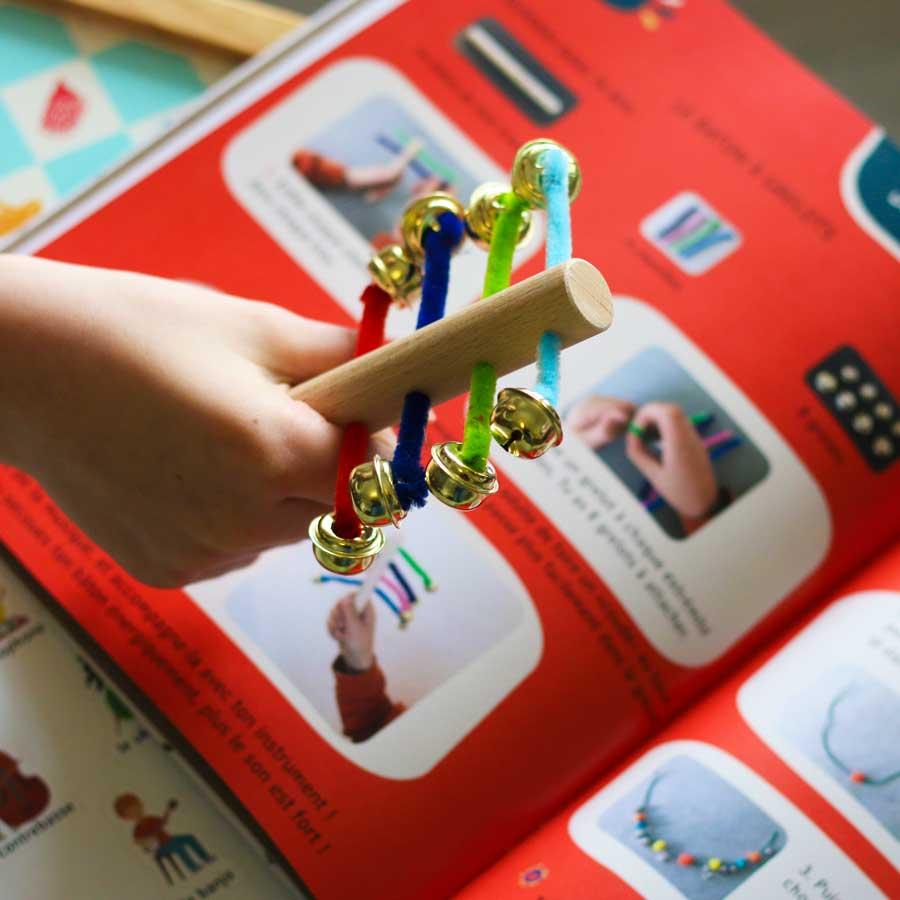 Petite main d'enfant tenant un instrument de musique qu'il a fabriqué - DIY - Activité ludique autour de la musique - matériel de loisirs créatif original pour fabriquer un instrumentActivité ludique autour de la musique - matériel de loisirs créatif original pour fabriquer un instrument