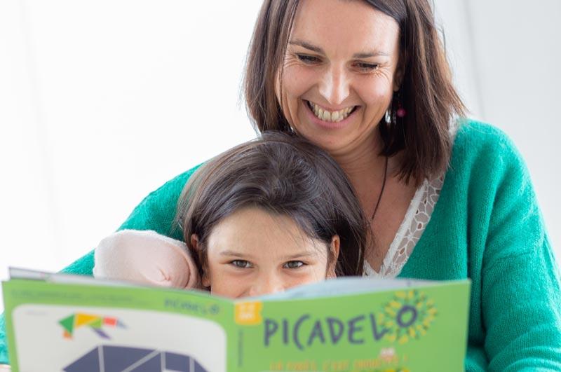Une maman et sa fille lisent ensemble un livre, magazine grand format avec illustrations de la box d'activités Picadelo pour enfant