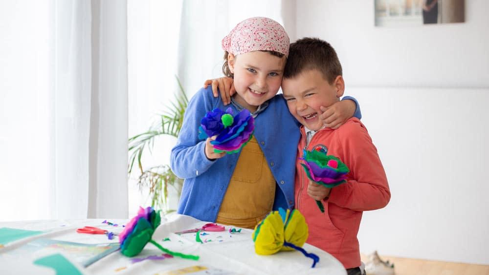 Enfants heureux qui rigolent en jouant avec les activités de la box picadelo pour enfant à la maison
