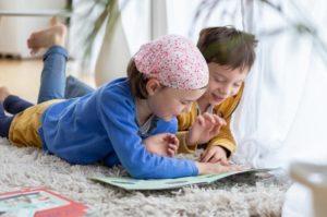 deux enfants lisent un magazine de la Box d'activités picadelo - Ils sont heureux et souriants, à la maison - Histoire dès 3 ans