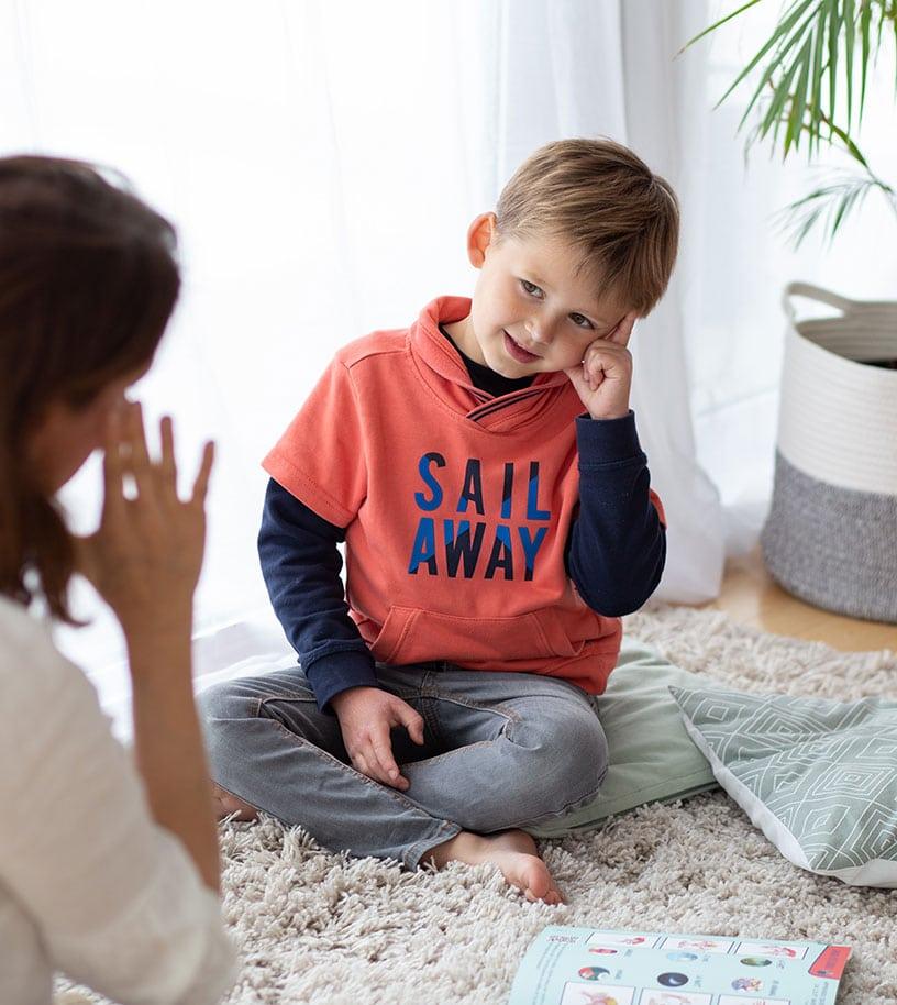 Un enfant, petit garçon apprend à signer - signe de la langue des signes